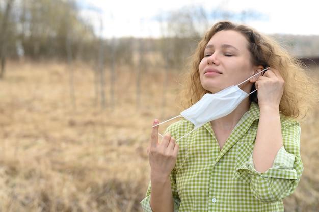 Terminando o conceito de isolamento e quarentena do vírus da coroa covid-19. jovem europeia de 30 anos remove uma máscara médica do rosto e respira ar fresco na natureza ao ar livre