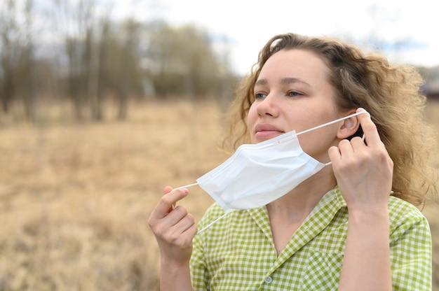 Terminando o conceito de isolamento e quarentena do vírus da coroa covid-19. jovem europeia removeu uma máscara médica do rosto e respira ar fresco na natureza ao ar livre