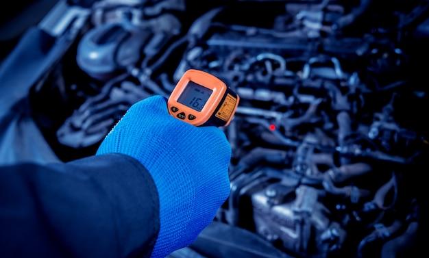 Termômetro a laser infravermelho na mão. medição da temperatura do motor