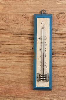 Termômetro antigo em um espaço de madeira