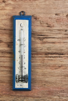 Termômetro antigo em uma mesa de madeira