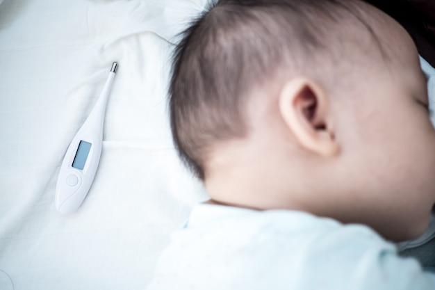 Termômetro com cabeça de bebê. fundo para bebê doente e doença conceito.