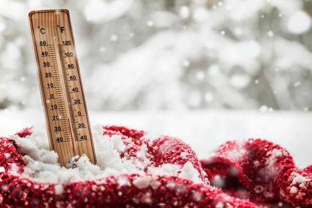 Termômetro com temperatura abaixo de zero sobressai em um monte de neve