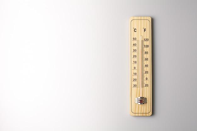 Termômetro de madeira calibrado em graus celsius e fahrenheit em fundo branco. - conceito de aquecimento global e clima.