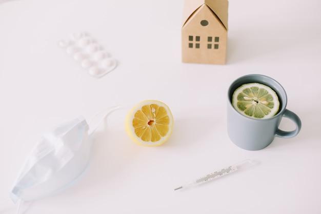 Termômetro de máscara médica e chá com limão conceito stay home coronavirus covid19