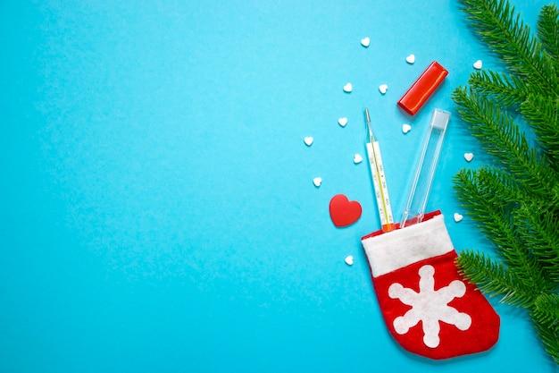Termômetro de mercúrio com comprimidos em forma de coração e coração vermelho e meia de natal papai noel com galhos de pinheiro sobre fundo azul