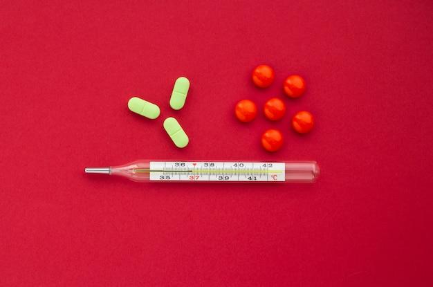 Termômetro de mercúrio com comprimidos laranja e verdes sobre um fundo vermelho, conceito de saúde