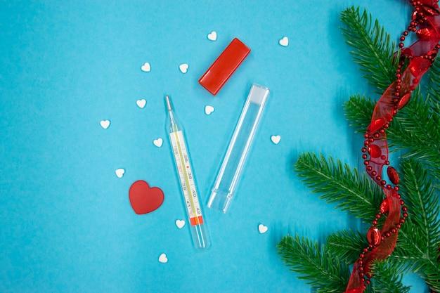 Termômetro de mercúrio de vidro com comprimidos em forma de coração e coração vermelho com ramos de pinheiro e decoração vermelha sobre fundo azul