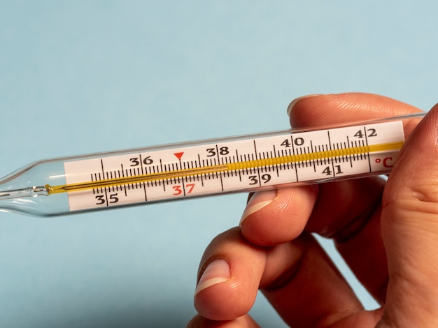 Termômetro de mercúrio em um fundo azul na mão. febre alta e doença
