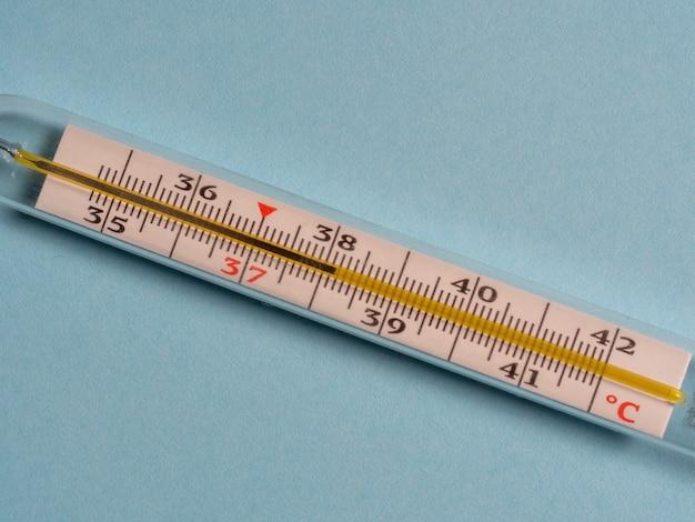 Termômetro de mercúrio em um fundo azul, vista superior. ferramenta para alterar a temperatura dos pacientes