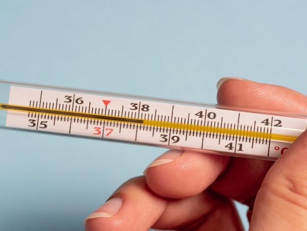 Termômetro de mercúrio na mão de uma mulher isolada em azul