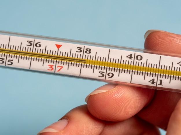 Termômetro de mercúrio na mão de uma mulher isolada em um fundo azul. medição de temperatura usando um termômetro. febre alta e doença. fechar-se