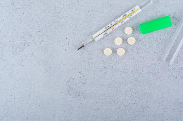 Termômetro e comprimidos médicos em mármore