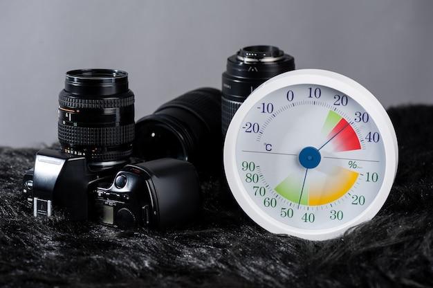 Termômetro e higrômetro analógico branco com equipamentos fotográficos.