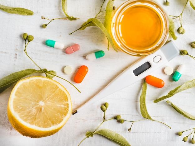 Termômetro elétrico, pílulas, limão. conceito de prevenção de resfriados