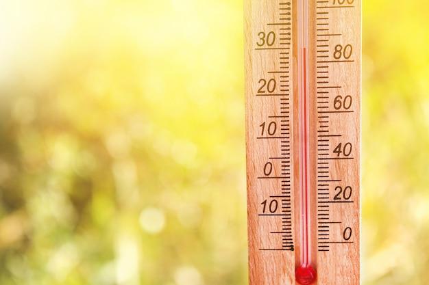 Termômetro exibindo altas temperaturas quentes de 30 graus no sol dia de verão.