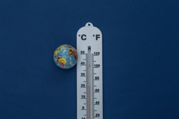 Termômetro meteorológico com globo sobre fundo azul clássico. cor 2020. visualização tiop