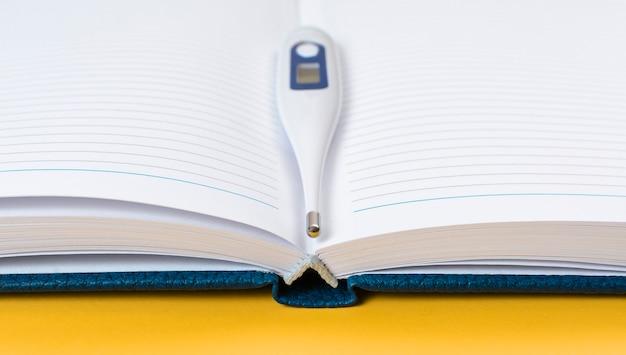 Termômetro nas páginas de um caderno aberto. conceito de gravação de medição de temperatura.