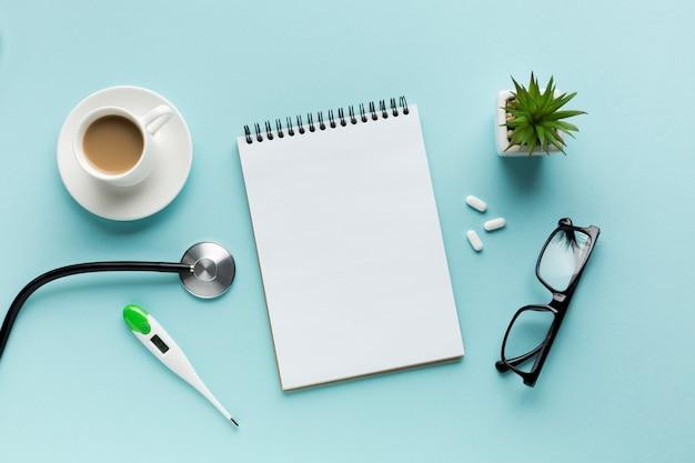 Termômetro; xícara de café; estetoscópio com bloco de notas em espiral; pílulas e óculos sobre a superfície azul