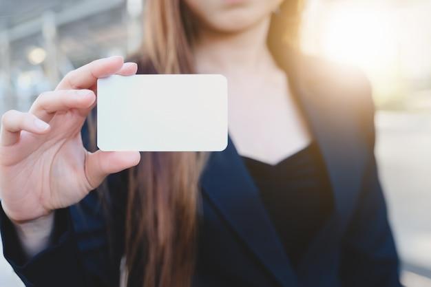 Terno de desgaste de mulher de negócios jovem segurando o cartão branco ou cartão de crédito em branco