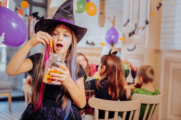 Terno de feiticeiro. aluna engraçada de cabelos escuros e fofa vestindo terno de bruxo para a festa de halloween comendo doces Foto Premium