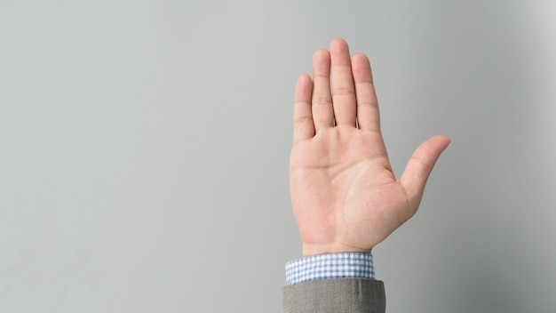 Terno de mão e palma vazia na cor de terno cinza sobre fundo cinza. empresário topic.close foto e estúdio tiroteio.