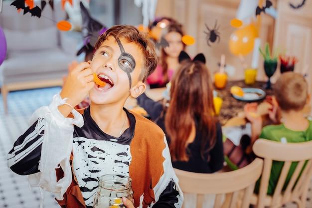 Terno de pirata. garoto bonito de cabelos escuros vestindo um lindo terno de pirata para a festa de halloween, sentindo-se entretido e feliz