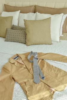 Terno e gravata na cama com travesseiros marrom e biege