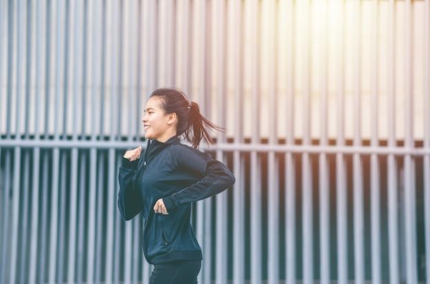 Terno preto de mulher jovem bonita asiática de tiro médio com feliz corrida ou corrida ao ar livre