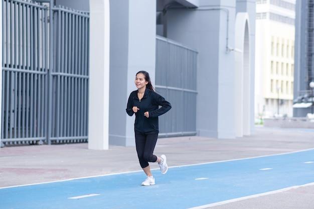 Terno preto de mulher jovem bonita asiática de tiro médio com feliz corrida ou corrida na pista de corrida.