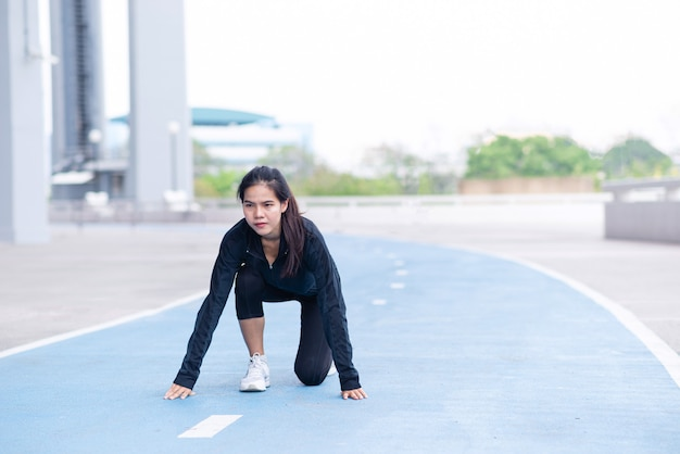 Terno preto jovem linda mulher asiática se preparando para começar a corrida.