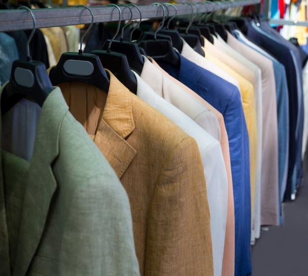 Ternos masculinos coloridos em linha em um cabide