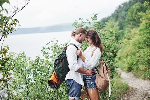 Ternura. jovem casal decidiu passar as férias de forma ativa perto do lago ao fundo.