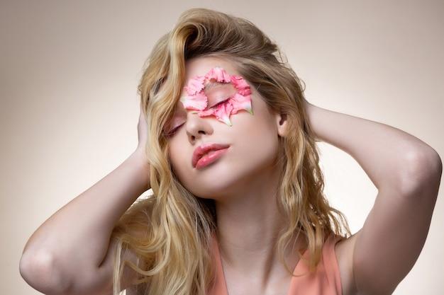 Ternura verdadeira. modelo delicado com viseiras rosa e pequenas pétalas rosa perto dos olhos mostrando poses