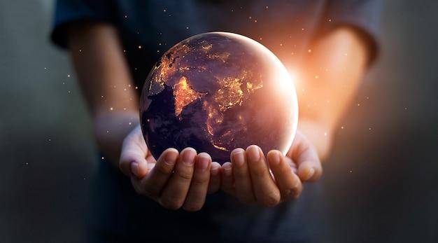 Terra à noite estava segurando em mãos humanas. dia da terra. conceito de economia de energia.