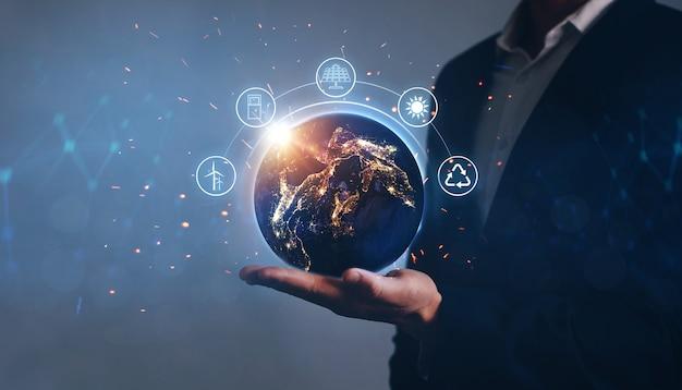 Terra da noite nas mãos do homem com ícones de fontes de energia renováveis. desenvolvimento ecológico. conceito de economia de energia.