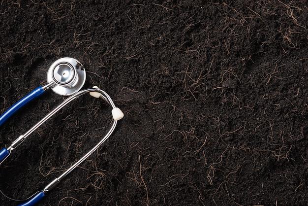 Terra preta para fundo de planta e estetoscópio médico