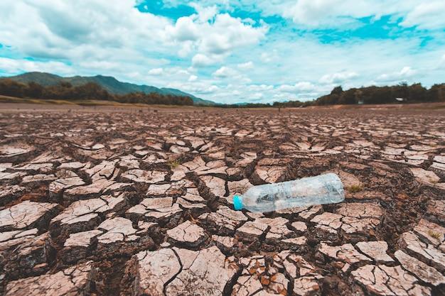 Terra seca rachada com garrafa de plástico vazia