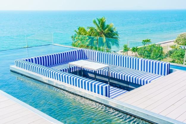 Terraço com azul e poltronas brancas e uma piscina ao redor