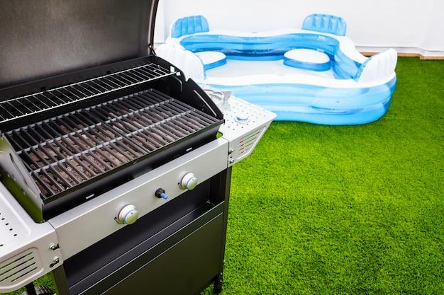 Terraço com grama artificial, churrasqueira e piscina de borracha para ficar em casa no verão.