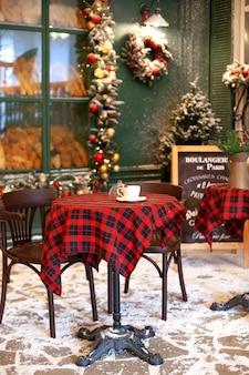 Terraço vazio do café com mesa de madeira e cadeira decorada para o natal.