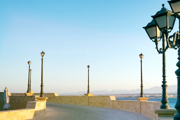 Terraplenagem de pedra com lâmpada de rua vintage perto do mar.