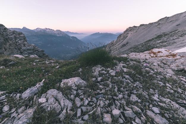 Terreno extremo da alta altitude, pico de montanha rochosa e cume entalhado, com o céu tormentoso dramático cênico.