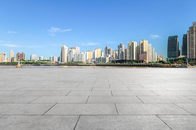 Terreno quadrado vazio e fundo de edifícios da cidade