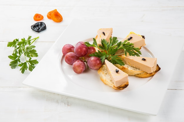 Terrina de foie gras delicioso com geléia de figo em uma mesa de madeira branca
