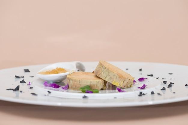 Terrine de fígado servido com molho doce, decorado com pétalas de flores, folhas verdes