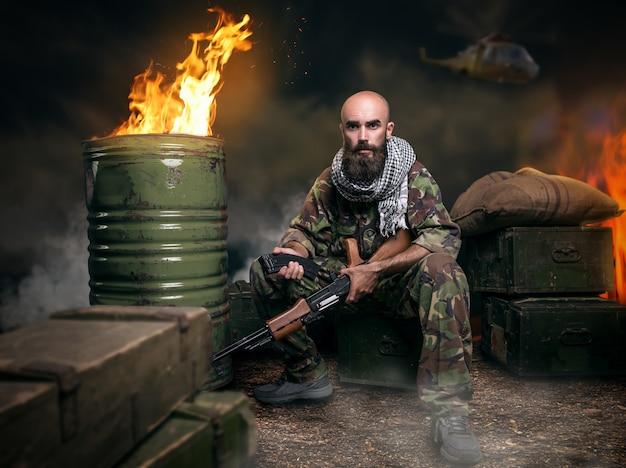 Terrorista barbudo em uniforme carrega arma