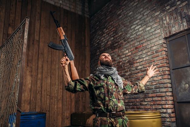 Terrorista com rifle kalashnikov levantando as mãos