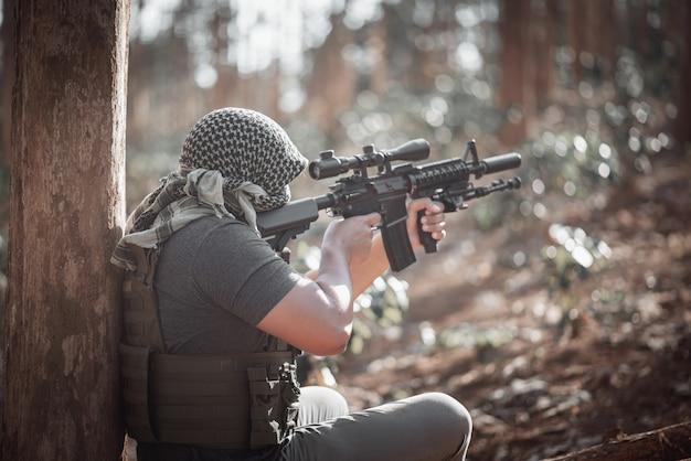 Terrorista de homem usando uma máscara e segurando uma arma, conceito de terrorista