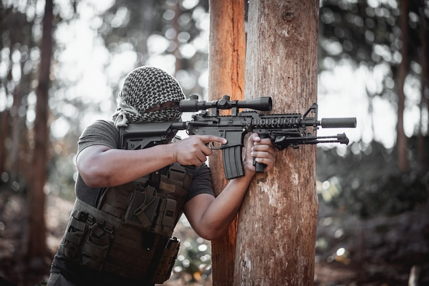 Terrorista de homem vestindo uma máscara e segurando uma arma, concpet terrorista